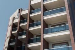 Alta costruzione moderna con i balconi contro un chiaro fondo del cielo Fotografie Stock