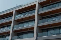 Alta costruzione moderna con i balconi spaziosi nei precedenti di chiaro cielo Fotografia Stock Libera da Diritti