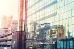 Alta costruzione moderna di vetro con il cielo blu e la nuvola al tramonto per Immagini Stock