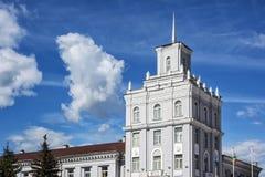 Alta costruzione quadrata con una guglia sul tetto sul backgr del cielo blu Fotografia Stock