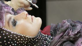 Alta-costura profissional O estilista cria uma imagem de um modelo na roupa com a ajuda de um aerógrafo e das pinturas filme