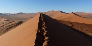 Alta duna con una piccola persona sopra  Fotografie Stock