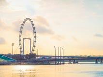 Alta e grande ruota di ferris sul lato del fiume di Singapore con i clo Immagini Stock