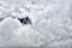 Alta e montagna ripida circondata dalle nuvole pesanti Immagini Stock