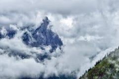 Alta e montagna ripida circondata dalle nuvole pesanti Fotografia Stock Libera da Diritti