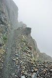 Alta e traccia alpina ripida e nebbia pesante in Glacier National Park Fotografie Stock