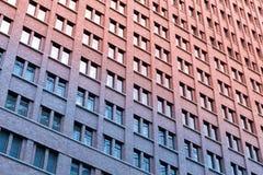 Alta facciata della costruzione di mattone di aumento - modello della finestra Fotografia Stock Libera da Diritti
