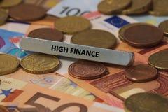 alta finanza - la parola è stata stampata su una barra di metallo la barra di metallo è stata disposta su parecchie banconote Immagine Stock Libera da Diritti