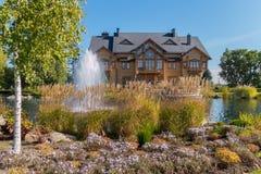 Alta fontana sul lago davanti ad una casa di legno con i balconi Fotografie Stock