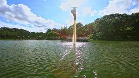 Alta fuente en el banco ancho de la silvicultura de la ondulación del agua del lago en parque