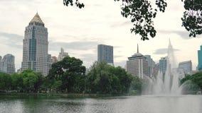 Alta fuente hermosa en la superficie del lago en el parque de la ciudad en fondo céntrico de los edificios Espray de la fuente q almacen de video