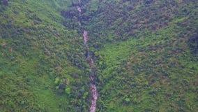 Alta garganta de la montaña de la visión aérea con la corriente entre selva