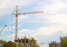 Alta gru gialla che costruisce una casa nel bello cielo blu luminoso con le nuvole Fotografia Stock Libera da Diritti