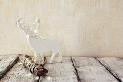 Alta immagine chiave di vecchio ceppo dell'albero con le luci di natale leggiadramente e di raindeer sulla tavola di legno Fuoco  Fotografie Stock
