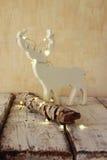 Alta immagine chiave di vecchio ceppo dell'albero con le luci di natale leggiadramente e di raindeer sulla tavola di legno Fuoco  Immagini Stock Libere da Diritti