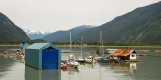 Alta marea ad un piccolo porticciolo ad una città costiera a distanza nell'Alaska Immagine Stock Libera da Diritti
