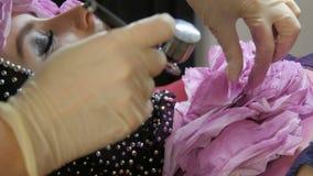 Alta moda profesional El estilista crea una imagen de un modelo en la ropa con la ayuda de un aerógrafo y de las pinturas metrajes