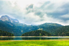 Alta montagna e lago nero al giorno nuvoloso, parco nazionale di Durmitor, Zabljak, Montenegro Fotografie Stock Libere da Diritti