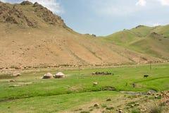 Alta montagna e una piccola azienda agricola con i yurts centroasiatici delle tende e River Valley stretto Immagini Stock Libere da Diritti