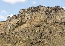 Alta montagna inaccessibile con il pendio pietroso contro il cielo blu con le nuvole, estreme Immagini Stock Libere da Diritti