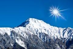 Alta montagna innevata con il cielo pieno di sole Immagine Stock Libera da Diritti