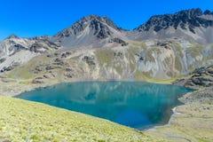 Alta montagna innevata e lago blu nelle Ande Fotografia Stock