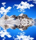 Alta montagna innevata oltre ad un lago con piacevole Fotografie Stock Libere da Diritti