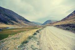 Alta montagna River Valley della tundra del deserto con la strada polverosa Fotografia Stock