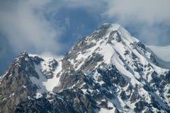Alta montagna rocciosa innevata Immagini Stock