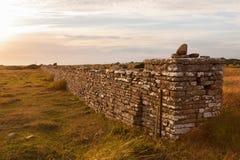 Alta pared de piedra en puesta del sol Fotos de archivo libres de regalías