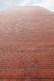 Alta parete della costruzione di mattone rosso luminosa e del cielo nuvoloso Fotografia Stock