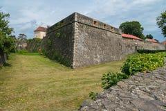 Alta parete di pietra della fortificazione con le finestre contro un fondo verde del prato inglese Fotografia Stock