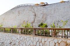 Alta parete di pietra leggera con le rotaie di legno e una roccia pura contro lo sfondo degli ombrelli dal sole e dal cielo blu i Immagine Stock