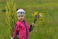 Alta pianta e una bambina in un prato Fotografia Stock Libera da Diritti