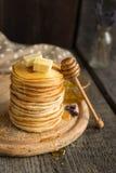 Alta pila de crepes deliciosas con mantequilla y miel Imágenes de archivo libres de regalías