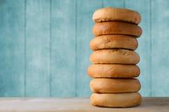 Alta pila del bagel su legno con il fondo del blu di turchese Fotografie Stock Libere da Diritti