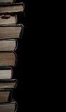 Alta pila di vecchi libri isolati su un fondo nero con spac Fotografia Stock