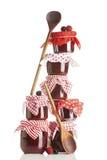 Alta pila irregolare di barattoli, di cucchiai e di bacche dell'inceppamento Fotografie Stock
