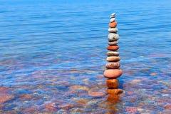 Alta piramide delle pietre colorate e bagnate che stanno in acqua Immagini Stock