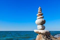 Alta piramide delle pietre dei colori differenti sui precedenti del mare e del cielo blu Immagine Stock