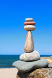 Alta piramide delle pietre dei colori differenti sui precedenti del mare e del cielo blu Immagine Stock Libera da Diritti