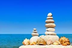 Alta piramide delle pietre e delle conchiglie bianche Oscilli lo zen nei precedenti del mare dell'estate Fotografia Stock
