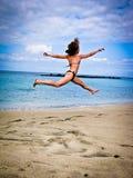 Alta ragazza di salto in un costume da bagno su fondo dell'Oceano Atlantico Fotografia Stock Libera da Diritti