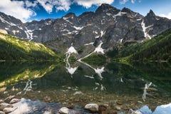 Alta riflessione dei peks nella superficie alpina del lago Fotografie Stock