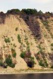 Alta riva sabbiosa del fiume, alberi verdi sulla cima Immagini Stock Libere da Diritti
