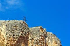 Alta roccia contro il cielo senza nuvole blu Fotografia Stock Libera da Diritti