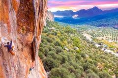 Alta roccia variopinta e due scalatori che salgono Fotografie Stock Libere da Diritti