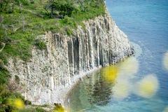 Alta roccia vicino al mare al fondo di una spiaggia rocciosa Fotografia Stock Libera da Diritti
