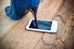 Alta scarpa che schiaccia un telefono cellulare Fotografia Stock Libera da Diritti