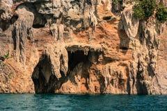 Alta scogliera con la caverna ed acqua sotto Fotografie Stock
